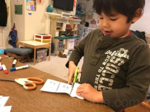 Child cutting out matching cards