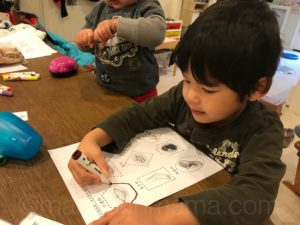 Child tracing shapes on Chinese worksheet
