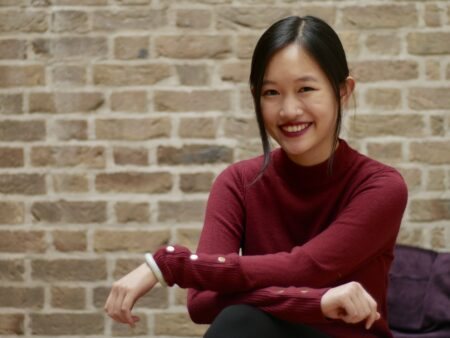 Smiling Asian American woman R.F. Kuang wearing a red shirt while sitting with her arms crossed.