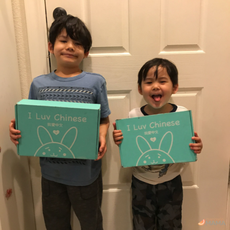 Two multiethnic Asian American boys holding I Luv Chinese boxes while standing against a door.