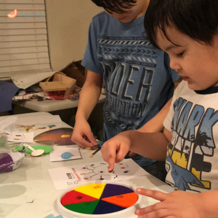 Two multiethnic multiracial boys doing I Luv Chinese crafts.