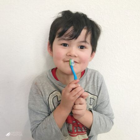 mutliethnic Asian American 4 year old boy holding a blue toothbrush to his smirking mouth.