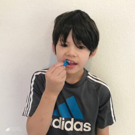Mutliethnic Asian American 7 year old boy using a blue floss pick.