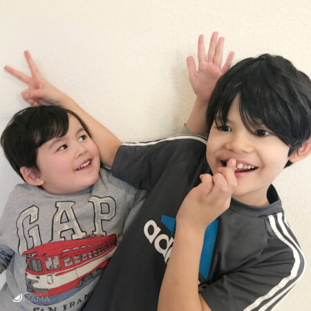 Two mutliethnic Asian American boys play fighting and giving each other
